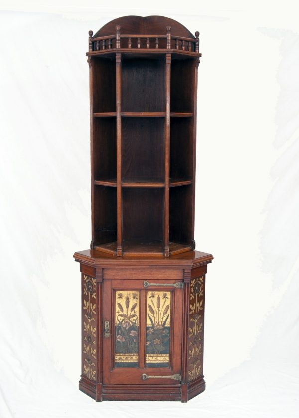 An Aesthetic Movement walnut corner cabinet, carved and painted. Circa 1880.