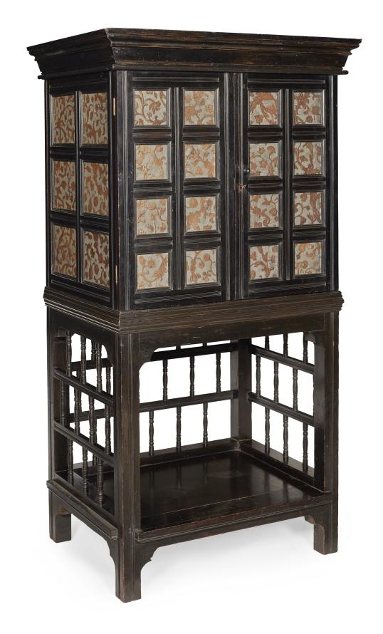An ebonised cabinet on stand, with patinated and gilded 'leather' paper.