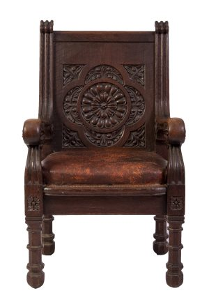 A carved oak chair with a carving in the back support and leather seat